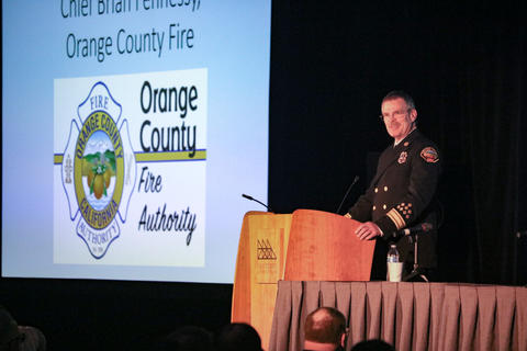 Chief Brian Fennessy presents on stage with his powerpoint presentation behind him