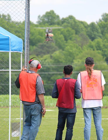 three men with their backs to the camera operate a drone hovering in the background