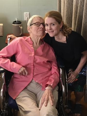 An elderly woman sits in a wheelchair next to a younger woman within a nursing home