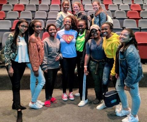 Jeanita Pritchett in an auditorium standing with a group of young girls.