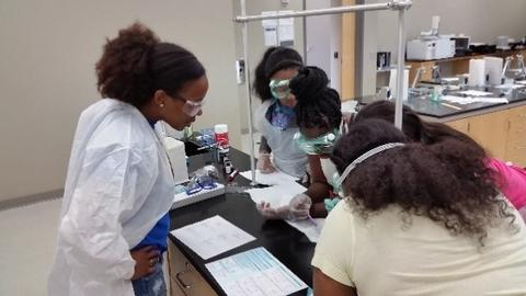 Jeanita and four young girls, all in safety glasses, stand around a lab table, their notebooks open.