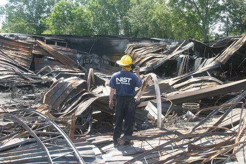 Man in NIST fire research t-shirt and hard hat standing among wreckage