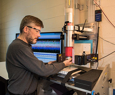 NIST Materials Scientist Michael Riley prepares a sample of material for a drop test that will reveal its ability to absorb and dissipate energy.