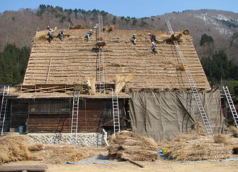 Workers are seen building a thatched roof on Japanese house.