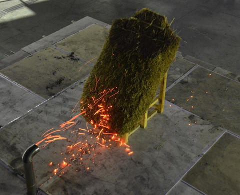 A rectangular-shaped model of a thatched roof is attacked by embers emitted from the pipe-shaped mouth of the NIST Dragon device.