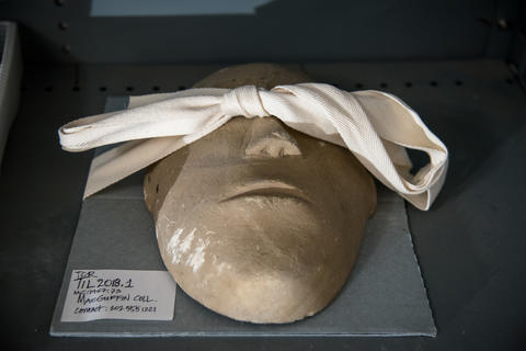a roughly made clay mask lying face up with a piece of cloth over its eyes
