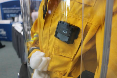 Mannequin in a case wearing a yellow jacket and wearable technology on their chest pocket