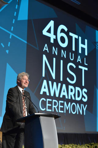 """A man stands at a podium in front of a large audience, and behind him a screen is lit up with the words 46th Annual NIST Awards Ceremony."""""""