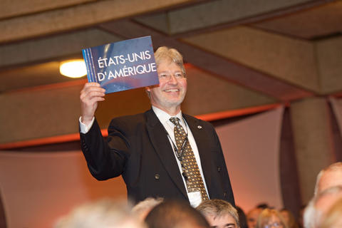Walt Copan holds up a card that says Etats-Unis D'Amerique