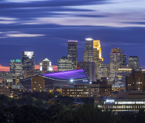 The darkened skyline of a city, with a stadium in the middle. The stadium glows purple.