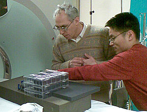 two researchers in front of CT scanner with box of polymer ellipsoids