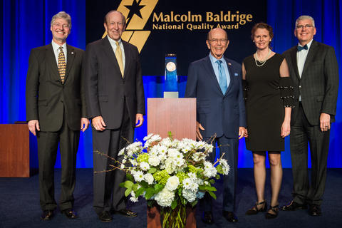 Center: Baldrige award on a podium. Left: 2 men in suits. Right: a man in a suit, woman in dress, man in suit