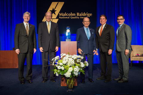 Middle: Baldrige Award on a podium. Left: two men in suits. Right: three men in suites