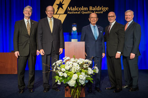 Center: Baldrige Award on a podium. Left: 2 men in suits. Right: 3 men in suites