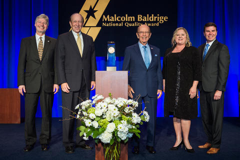 Center: Baldrige Award on a podium. Left: 2 men in suits. Right: man in suit, woman in dress, man in suit