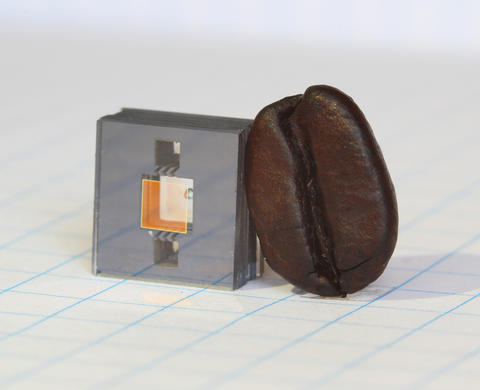 Square gray cube with two square holes in it and a gold square in between the holes, and a dark brown coffee bean leaning against the cube.