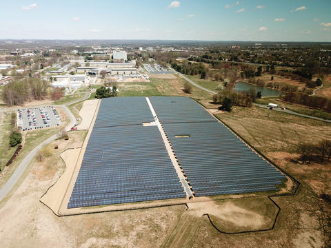 View from above, taken by a drone, of large array of solar panels on the campus of NIST near buildings and parking lots