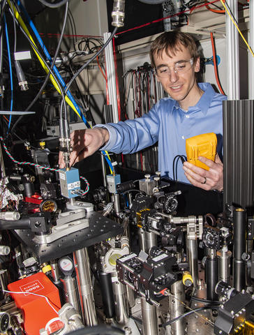Man wearing clear goggles holding a yellow box in one hand and using the other hand to adjust a table of optics equipment