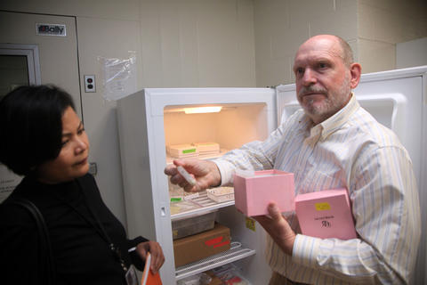 A man and a woman stand outside a freezer. The man is holding out a milk sample in a tube.