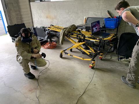 First responder using virtual reality with an EMT stretcher in the background.