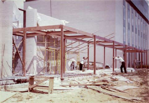 "A photo showing the construction of the ""breezeway"" in the 1960s. Two NIST ""wise guys"" clown for the camera by acting as though they're keeping the structure from collapsing."