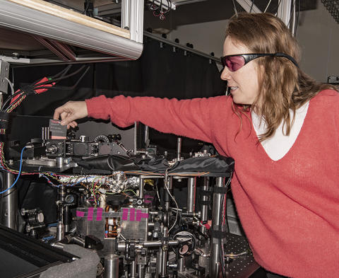 Woman with reddish hair and wearing a pink sweater and laser safety glasses reaching over an instrument table and holding a card used to path of lasers.
