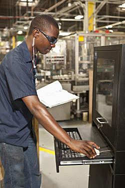 Man at Computer on Manufacturing Floor