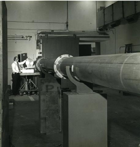 A man stands in the far background at the end of a long metal tube