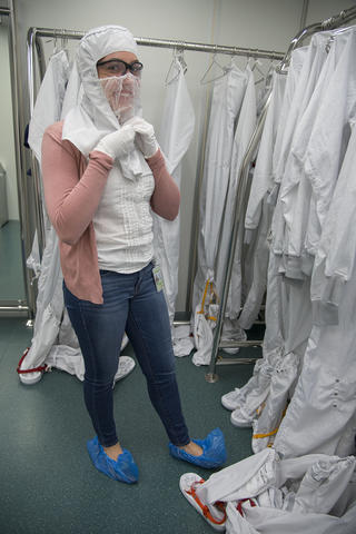 A woman puts on a clean room suit