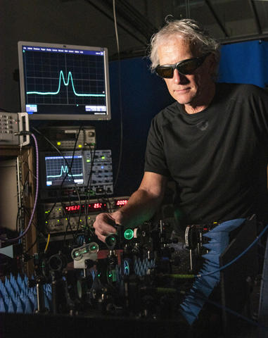 Man in black shirt and dark glasses facing camera is adjusting a mirror on a table of lasers and optics. On the left behind him are several electronics boxes topped by a computer monitor showing a blue signal that looks like cats ears.