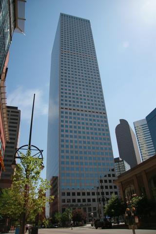 Dark skyscraper rises over a city