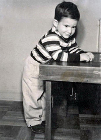 A small boy leans on a table