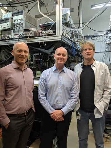 Image of Kyle Clark-Sutton (RTI), Alan O'Connor (RTI), and Dr. Chris Oates (NIST Boulder Group Leader, Optical Frequency Measurements Group), at NIST Boulder, after viewing the Ytterbium (Yb) Lattice Clock.