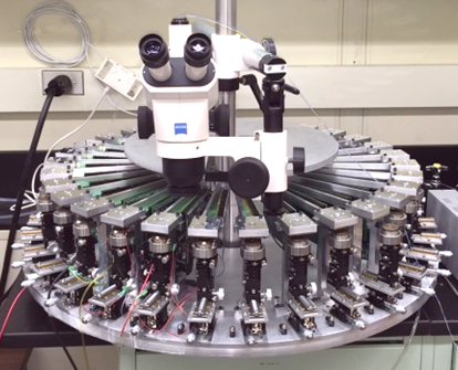 Massively parallel wafer-level long-term reliability test system featuring 30 fully functioning mini probe stations each supporting 100 probe pins with all the supporting stress/measure electronics integrated (without cables).