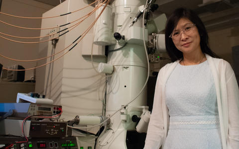 woman in a blue dress and white sweater stands next to an electron microscope