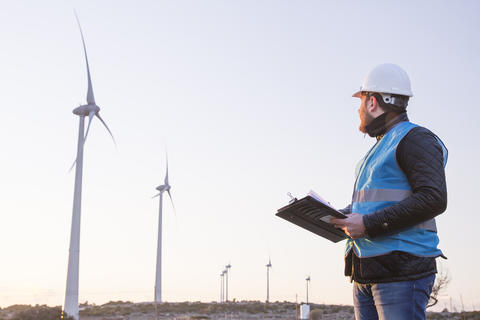 A man in a hard hard is holding a clipboard and looking towards a large wind turbine.