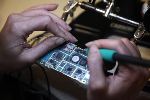 a person's hands as they use a soldering iron to attach wires to a circuit board.