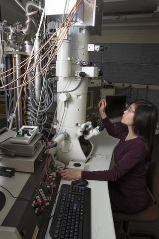 NIST researcher in a laboratory room looking at tall vertical microscope with multicolored wires emanating from it.