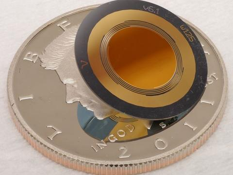 A disk-shaped device is smaller than the half-dollar coin underneath it.