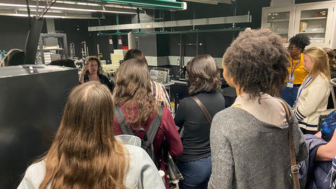 Amber McCreary giving a presentation in a lab to a group of female CUWiP attendees.