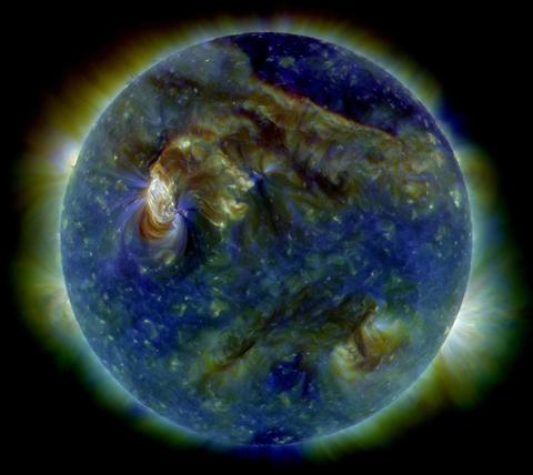 The Sun in EUV. The Sun appears mostly blue and purple with some areas of yellow. The sun is surrounded by a green/yellow corona.