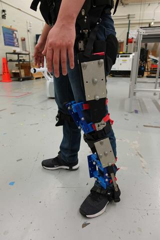 A person wears an exoskeleton and 3D-printed knee apparatus fashioned with reflective markers.