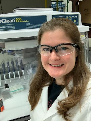 Megan Cleveland with white lab coat and safety glasses in front of a lab bench with pipettes.