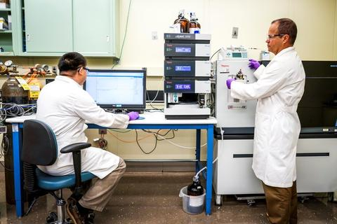 NIST research chemists Yuxue Liang (left) and Yamil Simon (right) in white lab coats acquiring data from a mass spectrometer.