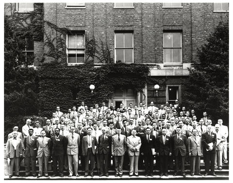 Men pose outside a brick building in a historical black-and-white photo.