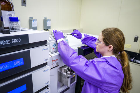 A woman in a purple coverall reaches up to work on scientific equipment.