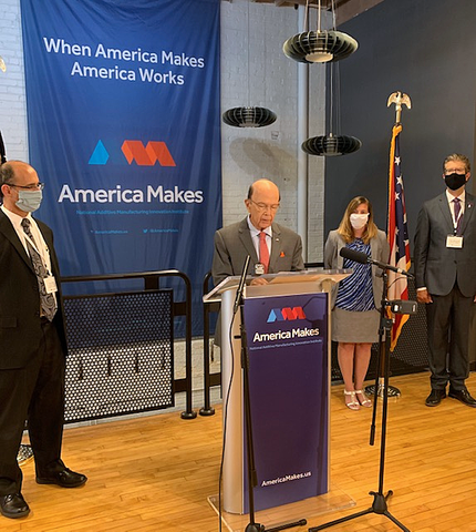 "A man stands at a podium labeled ""America Makes,"" with a man and woman at his left and a man on his right."