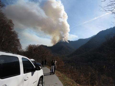 Onlookers view fire burning atop Chimney Tops mountain in Great Smoky Mountain National Park.