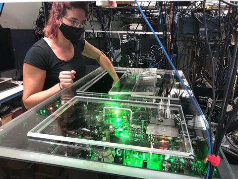 woman makes adjustments to optics on a laser bench