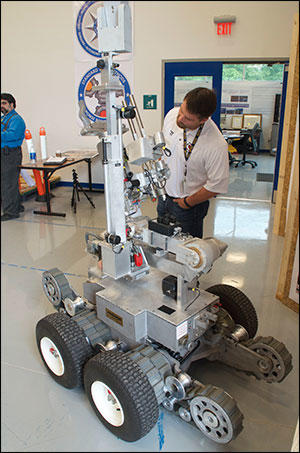 Matthew Hickman, Department of Homeland Security Program Manager, with a Remotec Andros bomb-disposal robot.